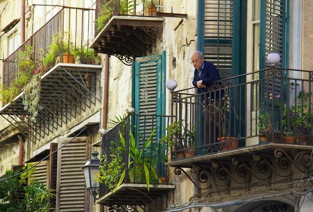 retraité qui regarde la rue depuis son balcon